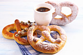 Sweet yeast dough pretzels for Easter on a napkin with a cup of coffee and catkins