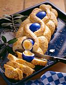 Pikanter griechischer Osterzopf aus Hefeteig mit Zwiebeln, Speck und blauen Ostereiern