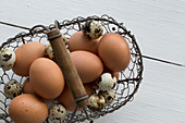 Hen's eggs and quail's eggs in a wire basket (seen from above)