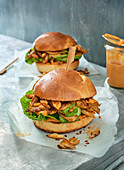 Two pulled chicken burgers on parchment paper
