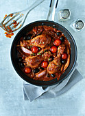 Mediterranean chicken legs with ingredients and sauce in a pan with a cruet