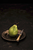 A pear on a tin plate with a knife