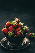 Strawberry in a metal bowl on a metal plate