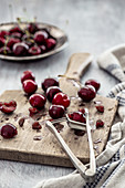 Cherry with a cherry pitter on a wooden board