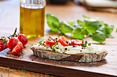 A slice of bread topped with cream cheese, tomatoes and cress