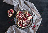 Red ripe peeled pomegranate on rustic metal plate