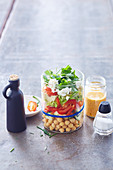 A layered salad in a jar with feta cheese and a mustard dressing