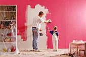 Vater und Tochter beim Malern im Kinderzimmer