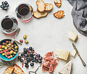 Variety of cheese, olives in blue ceramic bowl, prosciutto meat, roasted baguette slices, black grapes and glasses of red wine