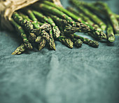 Fresh green asparagus over dark grey linen table cloth background