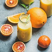 Healthy yellow smoothie with citrus fruit and ginger in bottle over grey concrete background
