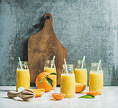 Healthy yellow smoothie with citrus fruit, ginger, ice in bottles on light marble table