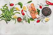 Flat-lay of raw salmon fish fillet steaks with vegetables, greens, rice and spices