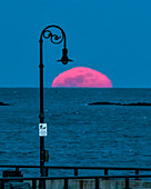 Full moon rising over ocean