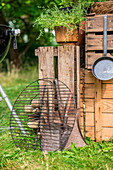 Barbecue grille next to outdoor kitchen made from wooden crated in summery garden