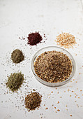 Zaatar spice mixture in a bowl next to its ingredients