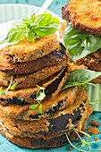 Fried aubergine slices, stacked, with fresh herbs