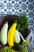 Various courgettes in a basket with fresh herbs