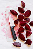 Beetroot cut in wedges with a knife on a chopping board