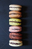 Six different macaroons against a dark blue background