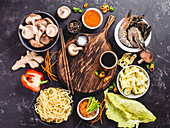 An arrangement of ingredients for an oriental noodle dish with prawns, mushrooms and vegetables
