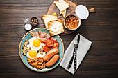 Englisches Frühstück mit Spiegeleiern, Speck, Würstchen, Bohnen und Toast