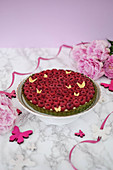 A raspberry tart with a green base and vanilla cream