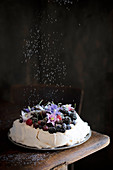 Icing sugar being sprinkled over a pavlova with berries and cherries