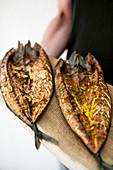 Zwei geräucherte Makrelen auf Holzbrett