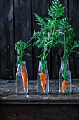 Fresh carrots in glass bottles