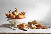 Conference pears in a colander and sliced on a wooden board