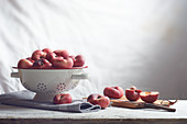 Flat nectarines in a colander and slices on a wooden board