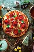 Pizza mit Käse, Salami und Cocktailtomaten