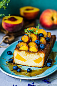 Cut fruitcake with peaches, blueberries and lavender, decorated with thyme