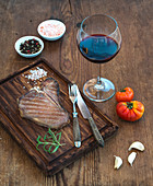 Cooked t-bone steak with garlic cloves, tomatoes, rosemary, spices and glass of red wine