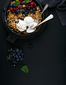 Healthy oat granola crumble with fresh berries, seeds, ice-cream and mint leaves