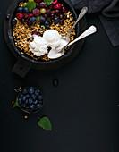 Haferflocken-Crumble mit frischen Beeren, Samen, Eiscreme und Minzblättern