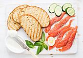 Gegrillte Brotscheiben, Räucherlachs, Hüttenkäse, Gurke und Basilikum
