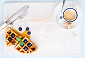 Espresso coffee cup and soft Belgian waffles with fresh blueberries and marple syrup