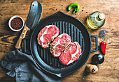 Uncooked rib eye roast beef steak on black iron grilling pan