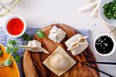 Verschiedene rohe Teigtäschchen auf Holzbrett daneben zwei Saucen (Aufsicht)