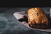 Fruit loaf on a linen cloth on a dark stone surface