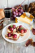 Geröstete rote Trauben auf gebutterten Brotscheiben