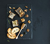 Honeycomb, walnuts, bread slices and honey dipper on black slate tray over grunge dark backdrop