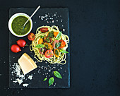 Spaghetti with pesto sauce, roasted cherry-tomatoes, fresh basil and parmesan cheese on black stone serving board over dark grunge backdrop