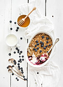 Healthy breakfast. Oat granola berry crumble with fresh blueberries, yogurt and honey in ceramic cooking dish over white rustic backdrop
