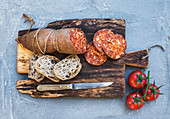 Wine snack set. Hungarian mangalica pork salami sausage, rustic bread and fresh tomatoes on dark wooden board