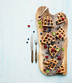 Soft Belgian waffles with berries, honey and mint on rustic wooden serving board over light blue background