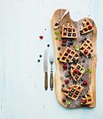 Belgische Waffeln mit Beeren und Honig auf rustikalem Brett