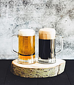 Light and dark beer in mugs on wooden board, grunge backdrop